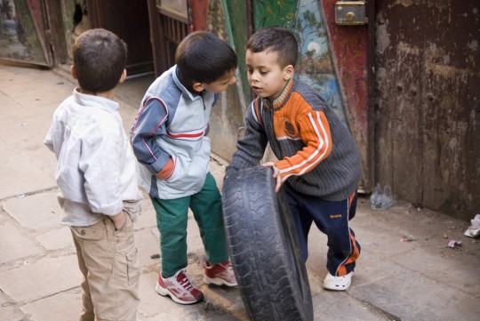 Kids fighting over a tire - Fez, Morocco